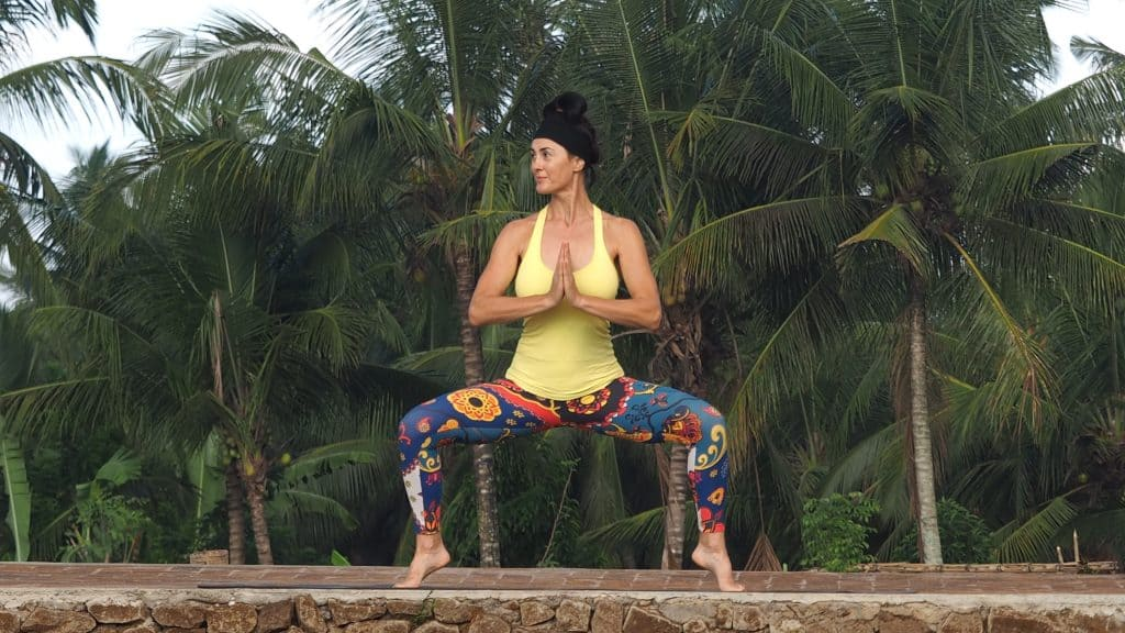 Elaine Reynolds Master Personal Trainer doing goddess squat with jungle background